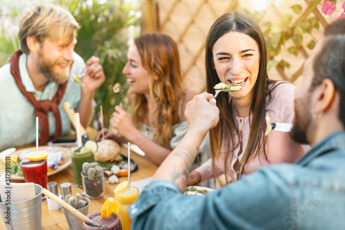 Fototapeta Happy friends lunching with healthy food in bar restaurant - Young people having
