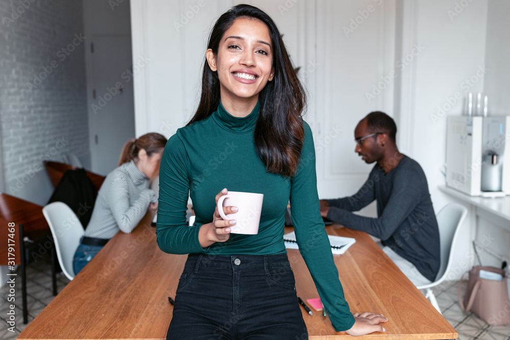 Fototapeta Young indian business woman entrepreneur looking at camera in the office.