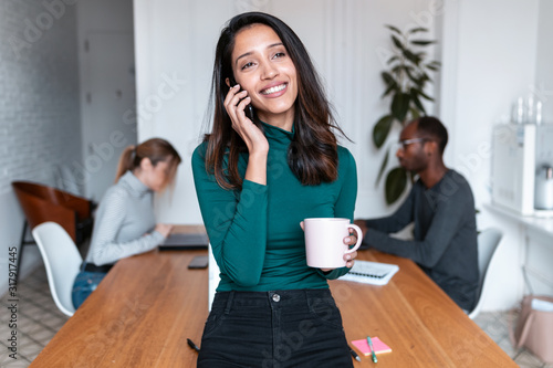 Valokuva Young indian business woman entrepreneur talking on mobile phone in the office