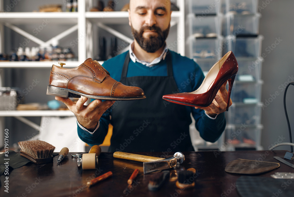 Fototapeta Bootmaker shows repaired shoes, footwear repair