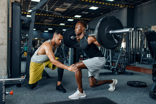 Muscular sportsman and trainer on training in gym Fototapeta