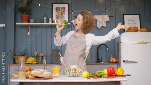 Young Happy Woman Singing And Dancing On Kitchen While Cooking Healthy Food Canvas Print