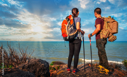 Fototapeta Young asian couple hikers climbing up on the peak of mountain near ocean. Two tourists with backpacks enjoying sunrise on top of a mountain. Climbing ,Helps and team work concept obraz