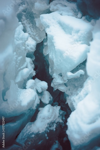 Fototapeta Vertical closeup shot of an ice crevasse in the snowy covered ground