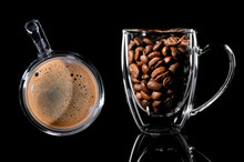 Composition Of Two Cups With Coffee. On The Left Is A Cup With Finished Coffee, Top View, On The Right Is A Cup With Coffee Grain Side View. Black Background
