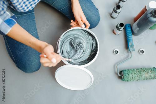Cuadros en Lienzo Female house painter mixes black and green paints