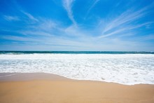 Beautiful View Of Ocean Waves Washing Over Beach Sand On A Warm Summer Day
