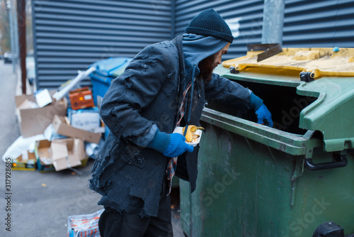 Male bearded beggar searching food in trashcan Fototapeta