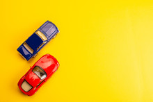 Two Toys Cars On Yellow Background