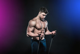 The athlete performs biceps exercises with the help of an expander