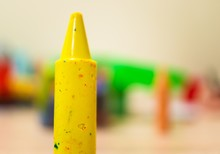 Closeup Shot Of A Yellow Crayon With A Blurred Background