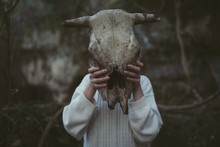 CLOSE-UP OF Woman Holding Animal Skull