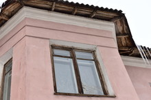 An Old Pink Building With Windows.