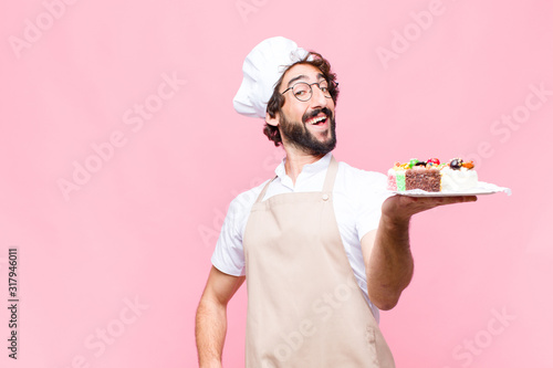 Photo young crazy baker man confectionery concept against pink wall