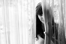 CLOSE-UP OF YOUNG WOMAN LOOKING THROUGH Fringe Curtain