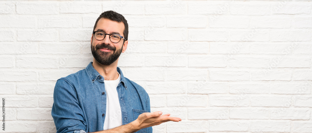 Fototapeta Handsome man with beard over white brick wall presenting an idea while looking smiling towards