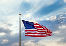 An American Flag On A Flagpole Against Blue Sky And Clouds