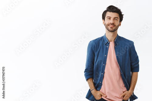 Fotografie, Obraz Cheerful, bearded handsome young man with messy hairstyle, standing relaxed in casual pose with hands in pockets, smiling, ordinary guy shopping in mall, buy gifts