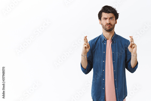 Photo Intense, skeptical handsome man cross fingers good luck but have doubts if dream