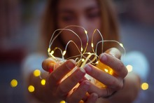 CLOSE-UP OF HAND HOLDING CHRISTMAS LIGHTS