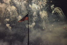 Low Angle View Of Flag Against Fireworks Exploding In Sky At Night