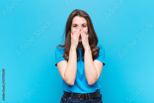 young pretty woman looking happy, cheerful, lucky and surprised covering mouth w Wallpaper Mural