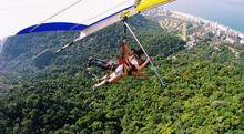 Man And Woman Hang Gliding Over Mountain