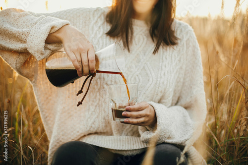 Fototapeta Hipster traveler pouring hot coffee in glass cup on background of rural herbs in sunset. Alternative coffee brewing outdoors in sunny light. Atmospheric rustic moment obraz