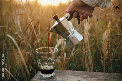 Fototapeta Traveler pouring fresh hot coffee from geyser coffee maker into glass cup in sunny warm light in rural countryside herbs. Atmospheric tranquil moment. Alternative coffee brewing in travel obraz