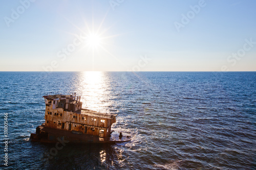 Sunken rusty cargo ship in still blue sea waters with bright sun over water horizon on summer clear day with blue sky Canvas Print