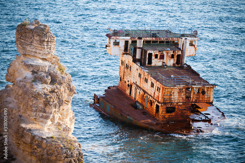 Photo Sunken rusty cargo ship in still blue sea waters with rocks around on summer clear day