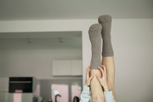 Low Section Of Woman Wearing Socks With Feet Up At Home