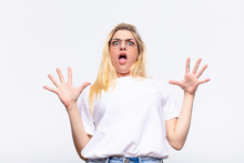 Young Pretty Blonde Woman Feeling Stupefied And Scared, Fearing Something Frightening, With Hands Open Up Front Saying Stay Away Against White Wall