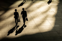 Top Aerial View Of Businessman Walk And Hold Briefcase In Work Time At Pedestrian. With Lighting And Shadow.