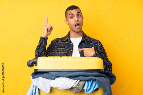 Traveler man with a suitcase full of clothes over isolated yellow background wit Wallpaper Mural