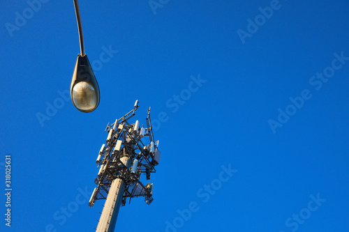 Cellular cell phone tower at sunrise set against a beautiful Blue morning sky Wallpaper Mural