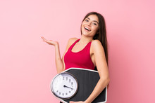 Pretty Young Girl With Weighing Machine Over Isolated Pink Background With Weighing Machine