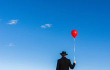 Rear View Of Man Holding Balloon Against Blue Sky
