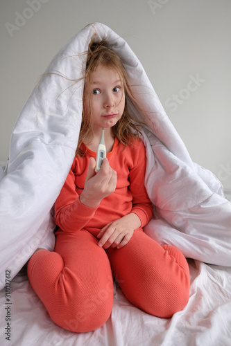 Valokuvatapetti little girl in sleepwear on a white bed sits with a thermometer and measures the