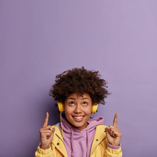 Glad Positive Woman Has Curly Hairstyle, Points Both Index Finger On Ceiling, Shows Copy Space Above, Has Good Mood As Listens Amusing Songs, Wears Stereo Headphones On Ear. Look Upwards, Please