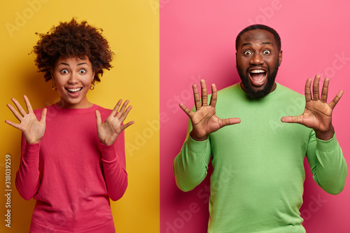 Indoor shot of overjoyed overemotive ethnic woman and man raise palms, stare emotionally, glad to see amazing surprise, open mouthes, wear pink and green clothes, stand over vivid two colored wall