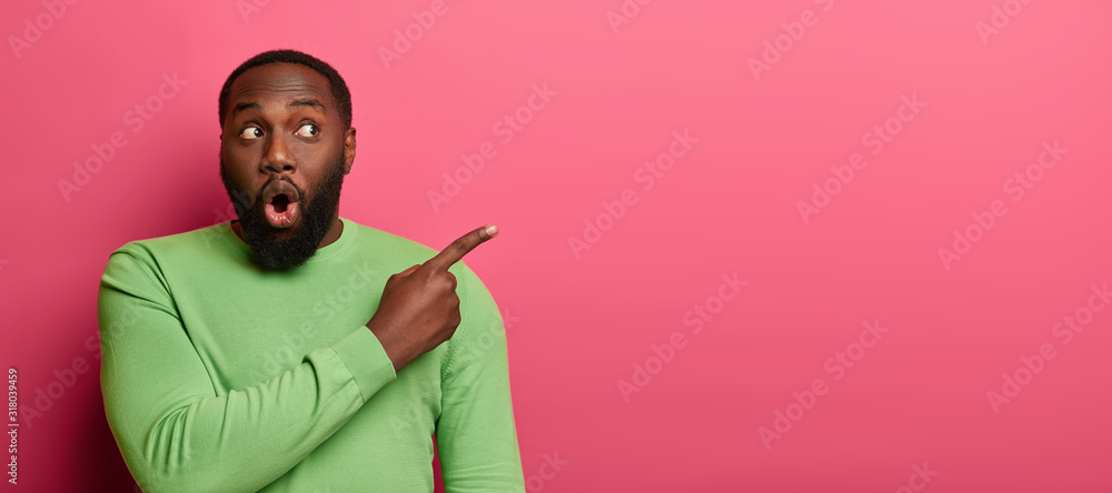 Fototapeta Shocked emotive bearded man with black skin, wears bright green sweater, points at empty space, surprised by unexpected relevation, demonstrates place on pink wall for your promotional content