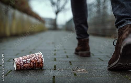 Fototapeta Mann wirft leeren Kaffebecher auf Gehweg obraz