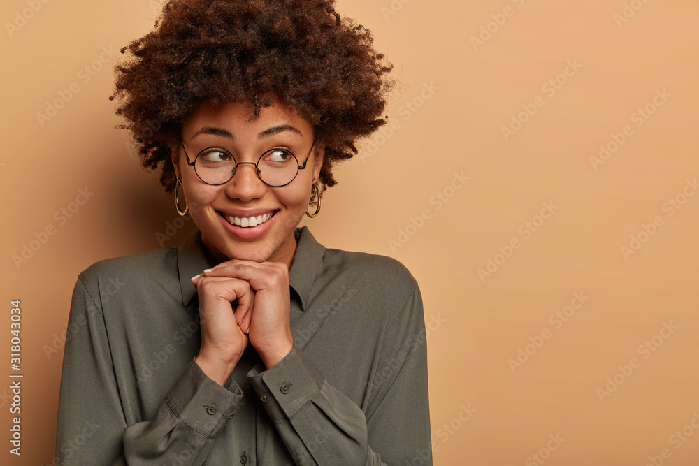 Fototapeta Optimistic lifestyle and emotions concept. Glad pretty young woman has gentle toothy smile, keeps hands together under chin, enjoys nice memorable moment in life, isolated over beige background