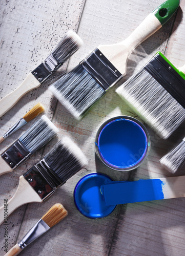 Paintbrushes of different size and paint can