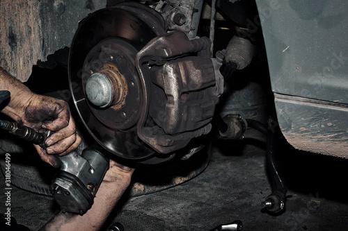 Mecánico reparando la transmisión y los frenos de un automóvil en el taller Wallpaper Mural
