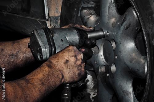 Mecánico cambiando la rueda de un automóvil en el taller. Canvas Print
