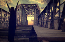 Silhouette Of Person With Raised Hands Praying On Old Abandoned Railway Metallic Bridge With The Sunset In The Background