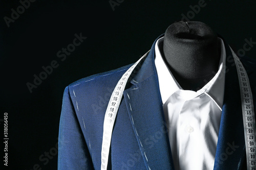 Photo Tailor's mannequin with unfinished clothes and measuring tape on dark background