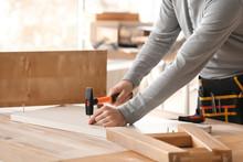 Handyman Assembling Furniture In Workshop